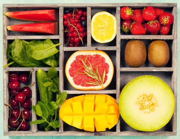 Gemüse und obst in holzkiste für vegane, glutenfreie, allergikerfreundliche, saubere ernährung und rohkost. blauer hintergrund und draufsicht