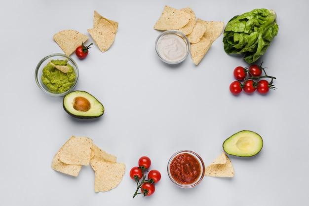 Gemüse und saucen in schüsseln zwischen haufen nachos