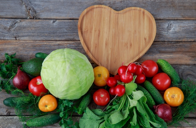Gemüse wird in einer reihe ausgelegt: kohl, zwiebeln, gurken, petersilie, dill, avocados, radieschen, tomaten und ein holzbrett in form eines herzens