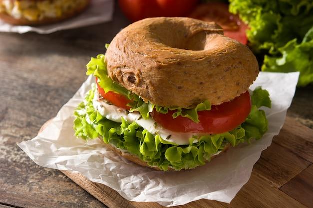 Gemüsebagelsandwich mit tomate, kopfsalat und mozzarellakäse auf holztisch.