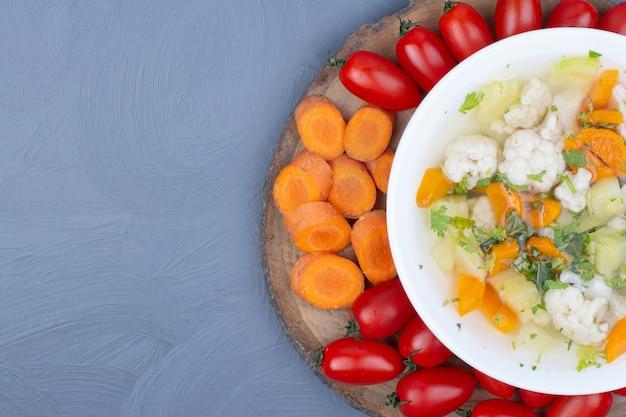 Gemüsebrühe suppe in einer weißen schüssel mit gehackten lebensmitteln