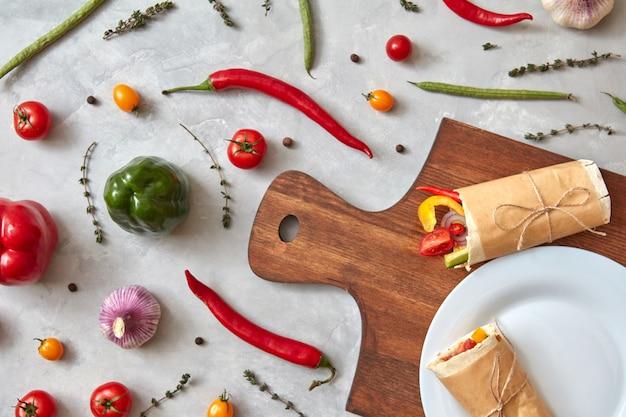 Gemüseburrito auf einem teller und auf einem holzbrett