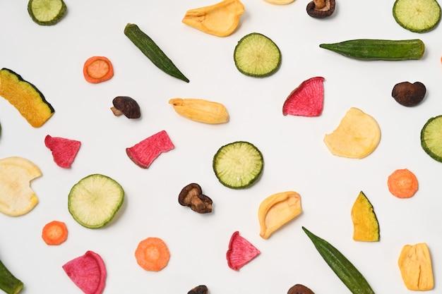 Gemüsechips auf weißem hintergrund mischen. veganes essen.