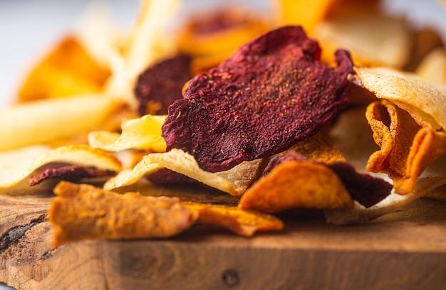 Gemüsechips aus kartoffeln, rüben und karotten auf einem holzbrett in nahaufnahme gelegt. selektiver fokus