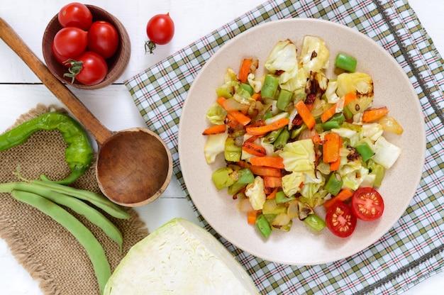 Gemüseeintopf eine mischung aus gebackenem kohl grüne bohnen zwiebeln karotten kirschtomaten paprika auf teller auf weißem holztisch