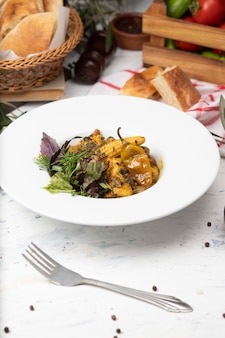 Gemüseeintopf mit fleisch, maisstücken, paprikapfeffer und gemüse, basilikum, petersilie in der weißen platte.
