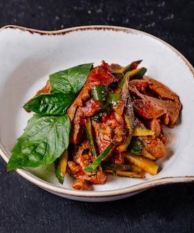 Gemüsefleischeintopfgericht mit basilikumblättern in einer weißen schüssel.