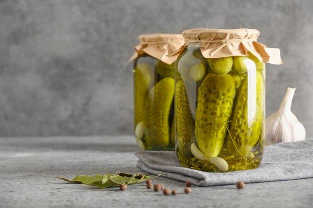 Gemüsekonserven gurke in gläsern auf grauem hintergrund