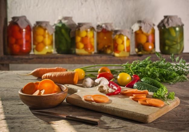Gemüsekonserven und frisches gemüse in gläsern