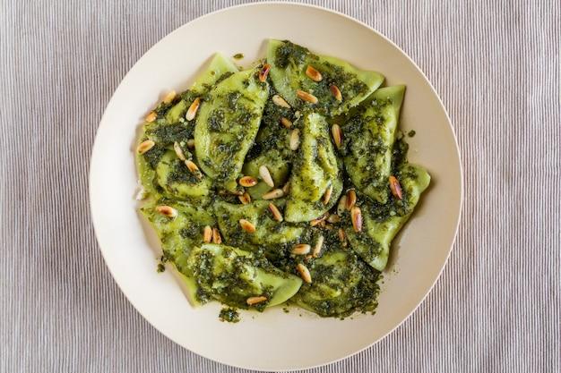 Gemüsemehlklöße mit pestosoße und gebratenen kiefernnüssen
