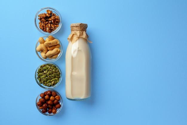 Gemüsemilchkonzept mit milchflasche und schalen mit körnern auf blau