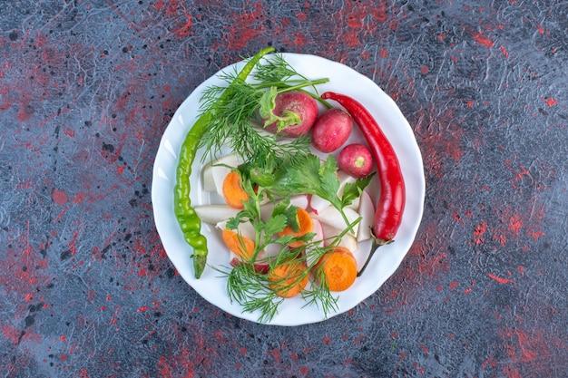 Gemüsemischung auf einer weißen platte auf schwarzem tisch.