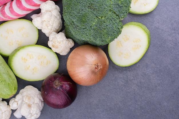 Gemüsemischung mit verschiedenen lebensmitteln isoliert auf blauer oberfläche
