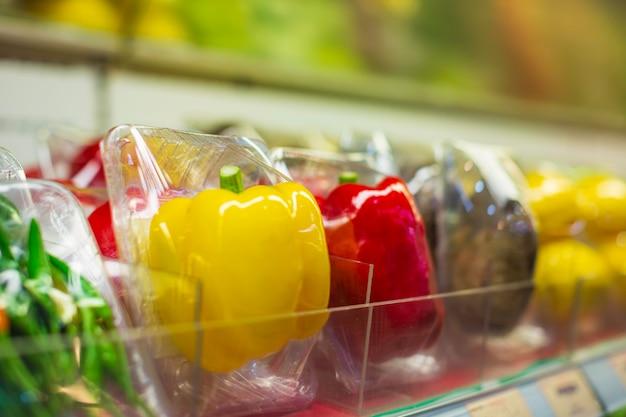 Gemüsepaprika des einkaufsregals, die sie bei lebensmitteln im supermarkt anziehen.