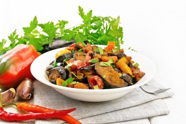 Gemüseragout mit auberginen, tomaten, süßen und scharfen paprika, zwiebeln, karotten, gebraten mit kräutern und gewürzen in einem teller auf serviette, knoblauch, petersilie auf holzbretthintergrund