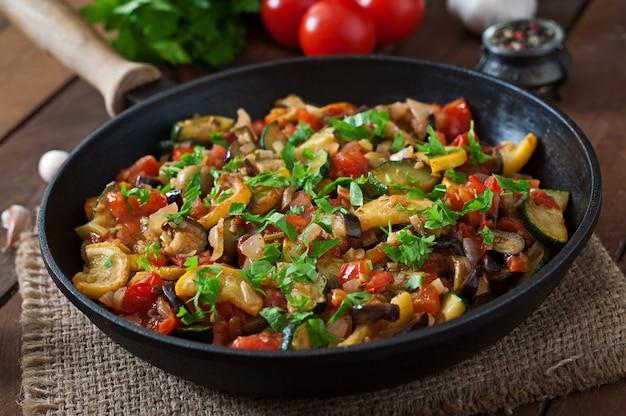 Gemüseratatouille in der bratpfanne auf einem holztisch