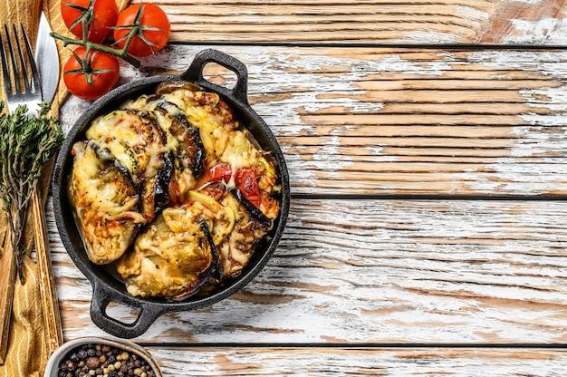 Gemüseratatouille in gusseiserner schale gebacken. holzhintergrund. draufsicht. speicherplatz kopieren.