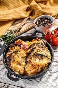 Gemüseratatouille in gusseiserner schale gebacken. holzhintergrund. draufsicht.