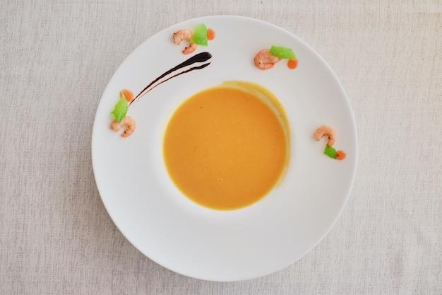 Gemüsesahnesuppe mit karotte in der weißen schüssel. draufsicht auf ein raues weißes tuch.