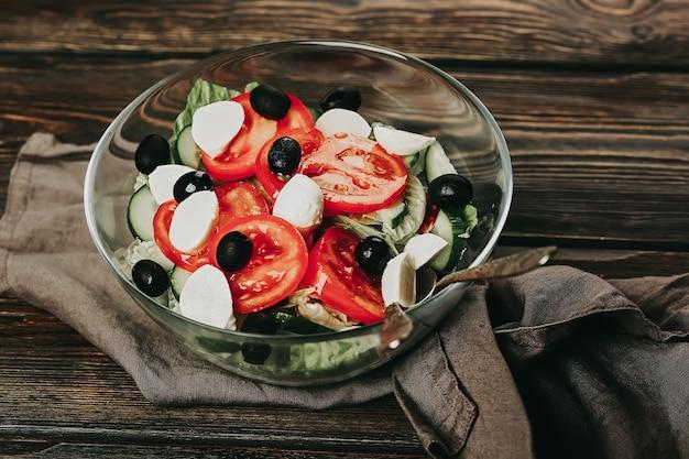 Gemüsesalat auf einem hölzernen hintergrund salat tomate gurke oliven mozzarella und olivenöl ganz...