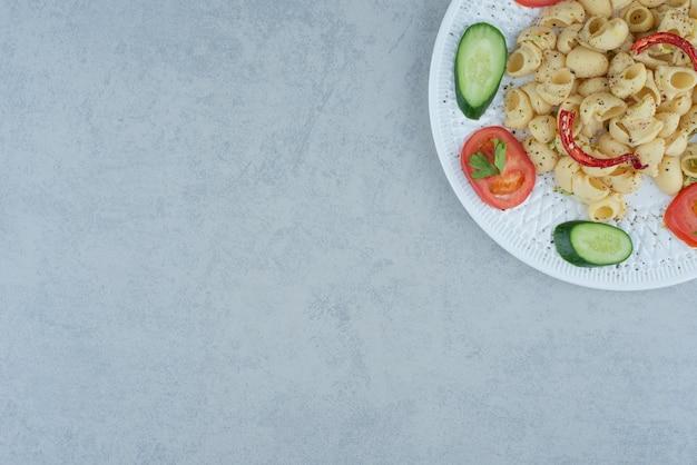 Gemüsesalat auf weißem teller mit köstlichen makkaroni auf marmorhintergrund