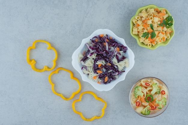 Gemüsesalat auf weißem teller mit makkaroni auf marmorhintergrund. hochwertiges foto