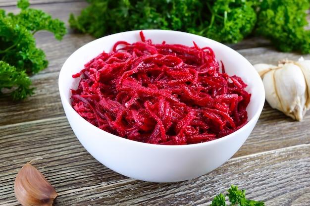 Gemüsesalat aus frischen rüben. koreanischer würziger salat in schüssel auf einem holztisch. ansicht von oben. vitamin-menü. vegane küche.