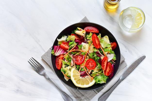 Gemüsesalat aus tomaten, spinat, salat, zwiebeln und paprika