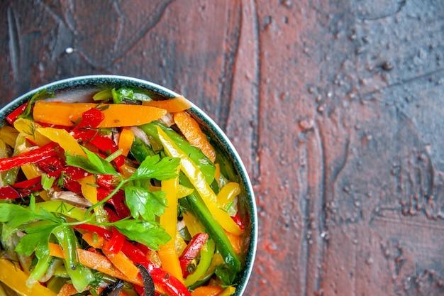 Gemüsesalat der oberen hälfte in der schüssel auf dunkelrotem tisch mit kopierplatz