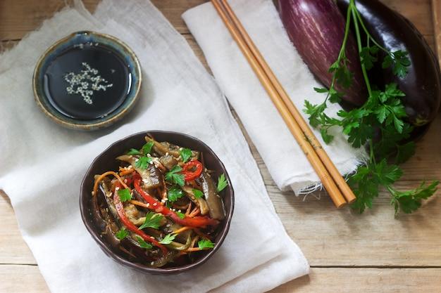 Gemüsesalat der orientalischen art mit aubergine, sojasoße und essstäbchen auf einem holztisch. rustikaler stil.