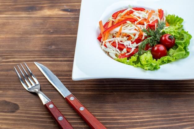 Gemüsesalat der vorderansicht mit grünem salat und kohlinnenplatte auf brauner oberfläche