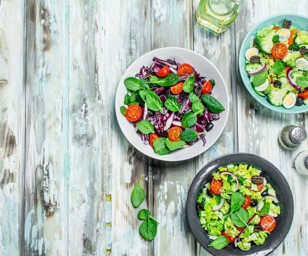 Gemüsesalat. eine vielzahl von bio-salaten, gemüse mit olivenöl und gewürzen. auf einem rustikalen.