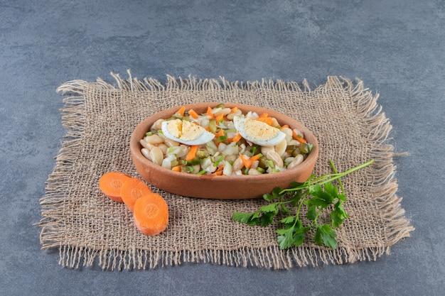 Gemüsesalat in der schüssel auf einer leinenserviette auf der marmoroberfläche