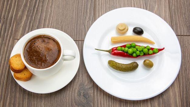 Gemüsesalat in dosen und eine tasse schwarzen kaffee mit rotem pfeffer und crackern auf tellern