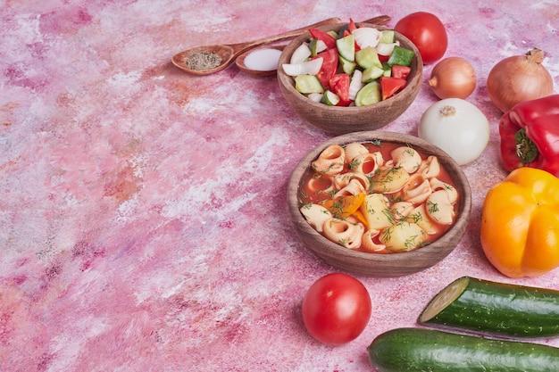 Gemüsesalat in einer holztasse mit einer schüssel nudelsuppe.