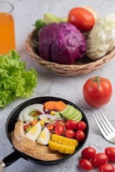 Gemüsesalat mit brot und gekochten eiern in der pfanne.