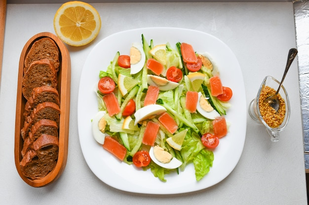 Gemüsesalat mit brot und senf. auf einem weißen teller. von oben betrachten