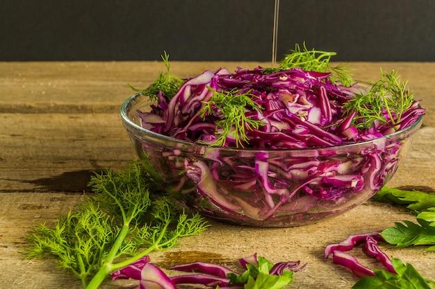 Gemüsesalat mit frischem rotkohl und gewürzen, auf hölzernem baclground.