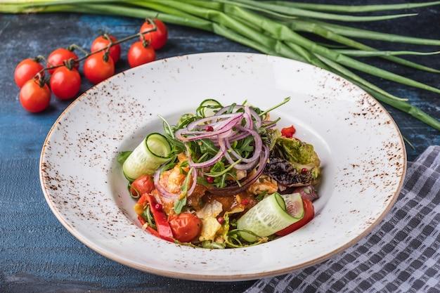Gemüsesalat mit frischen gurken, marinierten tomaten, salat, rucola und zwiebeln.