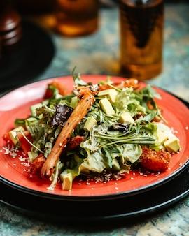 Gemüsesalat mit gebratenem schiffsgrün avocado-paprika-salat und brotstangen auf teller