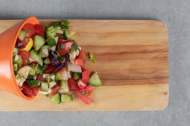 Gemüsesalat mit gemischten zutaten auf einem holzbrett.