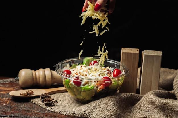 Gemüsesalat mit geriebenem käse und tomaten, gewürzt mit mayonnaise