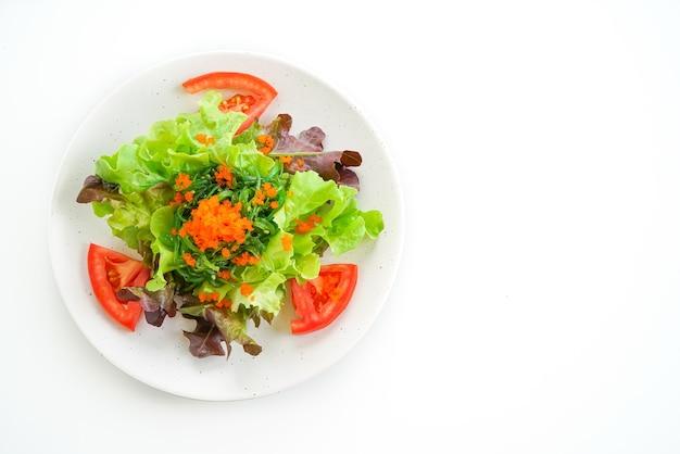 Gemüsesalat mit japanischen algen- und garneleneiern auf weiß