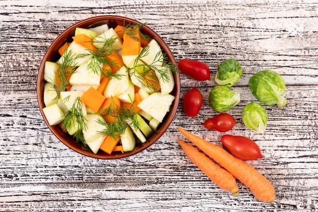 Gemüsesalat mit karotten und rettich in einer keramikschale auf weißem holztisch