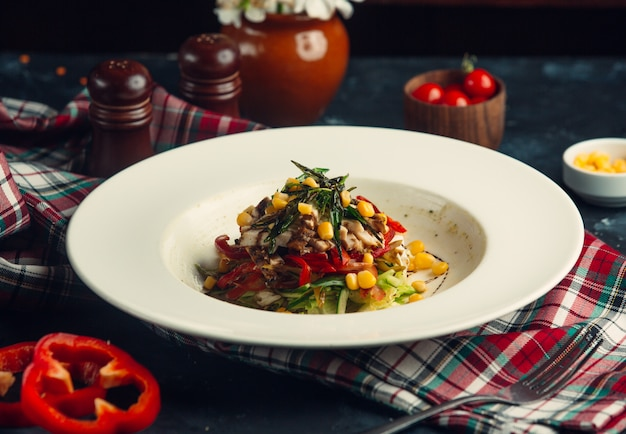 Gemüsesalat mit kräutern, rotem grünem pfeffer und maissamen.