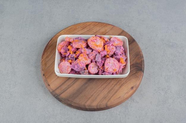Gemüsesalat mit lila rote beete und orange gehackten karotten gemischt mit saurer sahne.