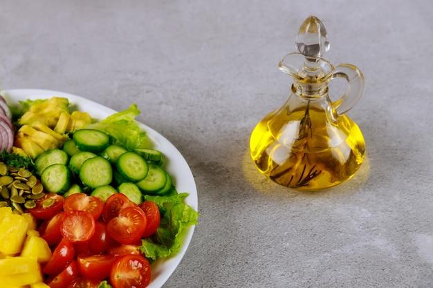 Gemüsesalat mit olivenöl in glasflasche