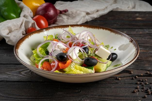 Gemüsesalat mit salat, oliven, rotem paprika, kirschtomaten, zwiebelringen, gurke und feta-käse.