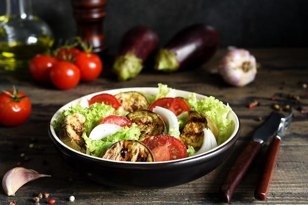 Gemüsesalat mit salat, tomaten und gegrillten auberginen auf dem küchentisch.