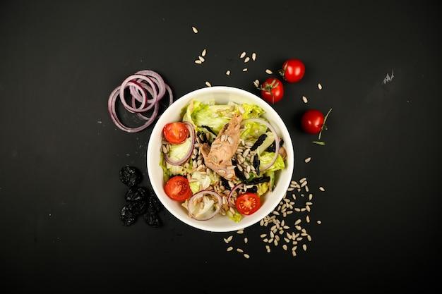 Gemüsesalat mit thunfisch und seitlichen zwiebelscheiben draufsicht